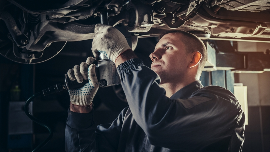 Mechanic inspecting car with extended warranty